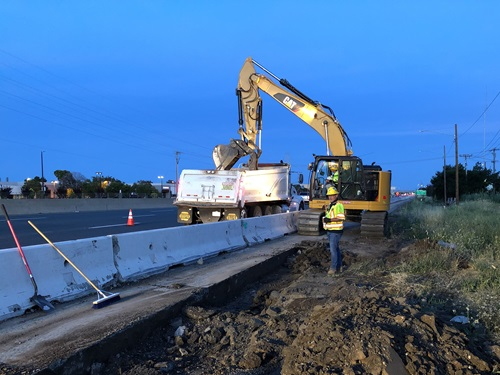 Construction crews excavating material from the freeway shoulder