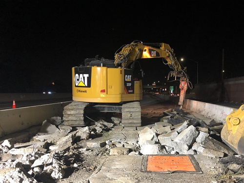 Construction crews demolishing concrete to create a new section of roadway