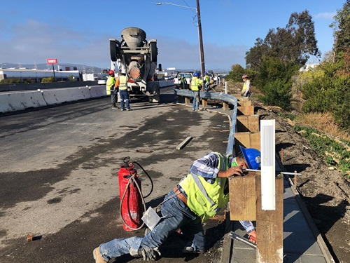 Construction crews installing new guardrail