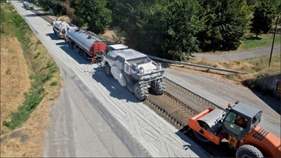 aerial view of a full depth reclamation train performing work on pavement during day construction