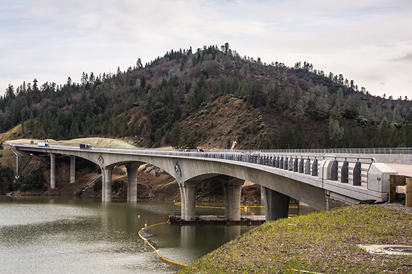 View of a bridge crossing a river that is supported by an alternating pattern of pillars and an arches.