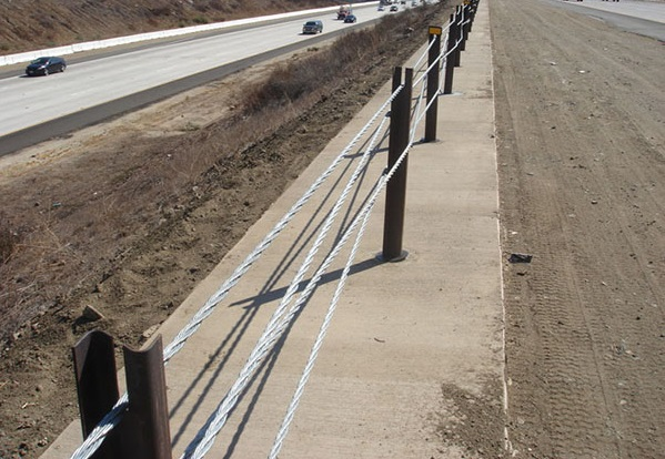 View of a multi-late freeway from the center median. The median divider is made of large steel posts with multiple steel wires woven between them.