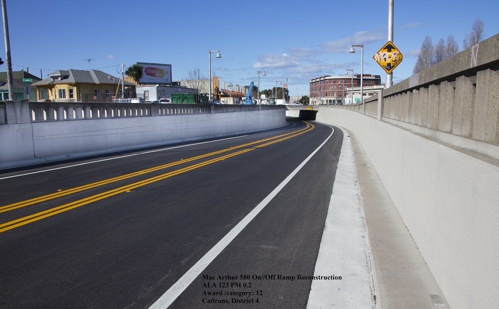 A newly paved two lane highway with historic-looking cement barriers on either side of the road.