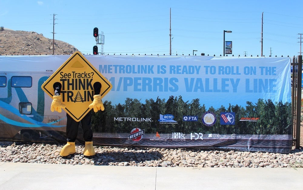 A large sign with information about the MetroLink program with a mascot dressed as a railroad sign in the foreground.