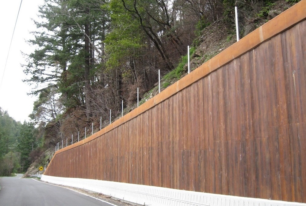 A view of a plank wooden wall with a hillside, trees and shrubs above and behind the wall.