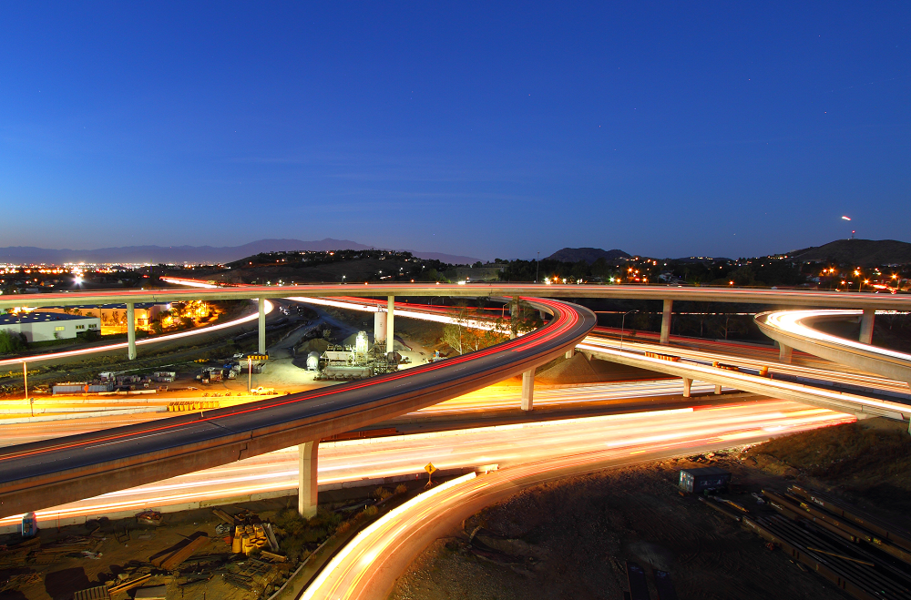 A view of several freeways curving and interweaving with cars driving by in a blurred motion.