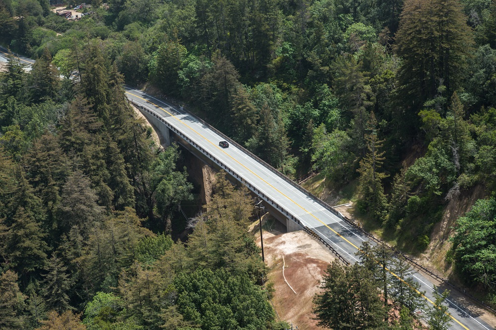 From above, a view of a highway bridge spanning a large tree-filled valley.