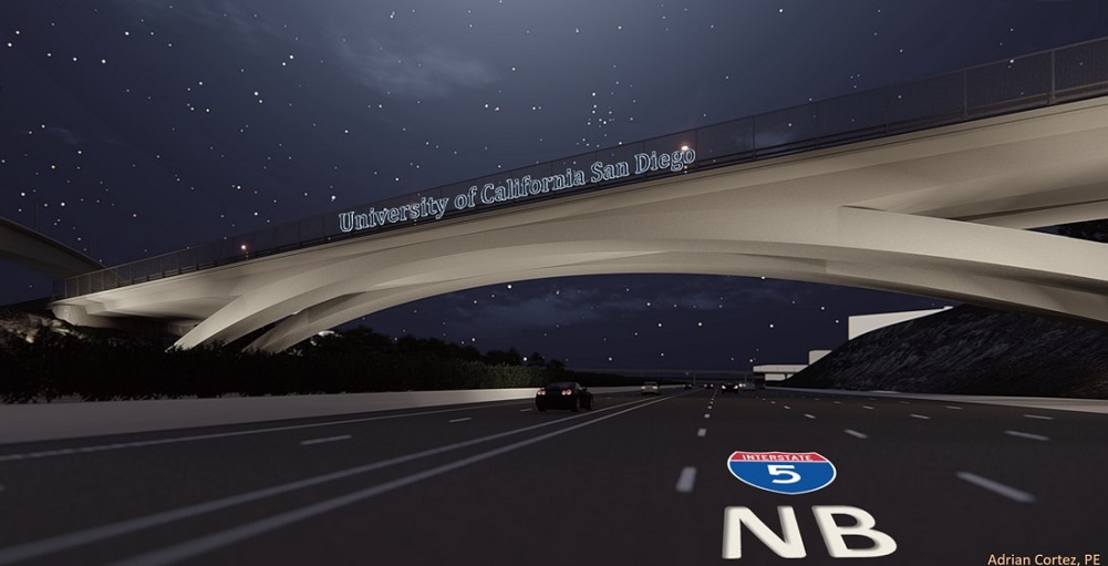 A night-time view of a freeway from the perspective of a car driving underneath a well-lit bridge with the words 'University of California San Diego' on the bridge.