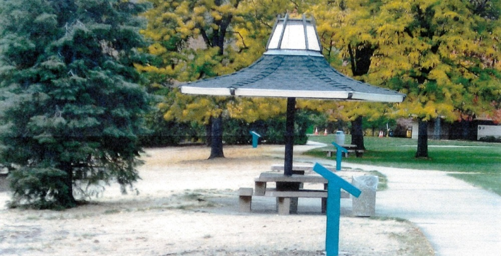 A side-view of a rest area with signage and a gazebo with picnic table underneath it. Trees are in the background.