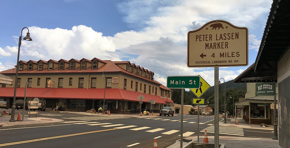View of a newly paved 4 way intersection with a sign indicating the way to the historical landmark 'Peter Lassen Marker'.