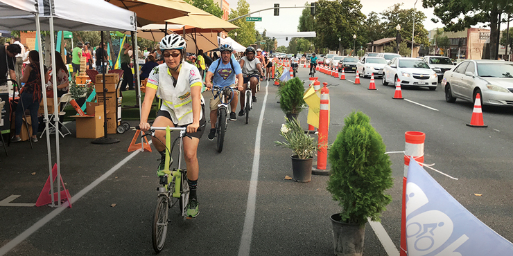 Photo of numerous cyclists in a bike lane during a street event