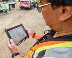 A Caltrans transportation engineer inspects a handheld tablet at a job site
