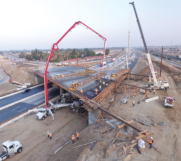 Aerial photo of workers and a crane lifting materials during construction of new overpass