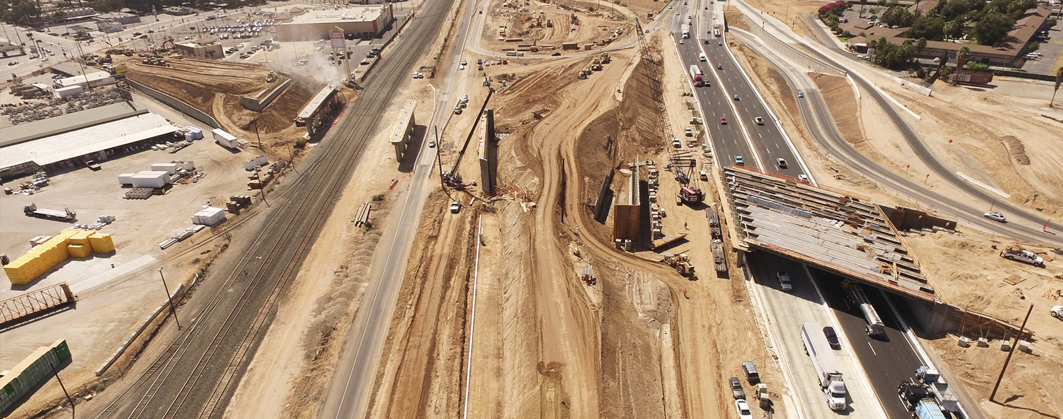 Aerial image of the early phase of construction, showing heavy equipment and a portion of a new overcross