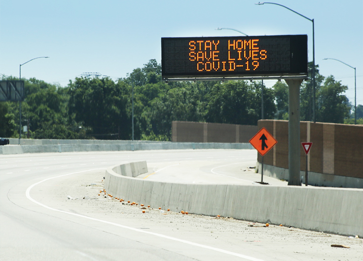 "Photo of a changeable message sign reading, ""Stay Home, Save Lives, COVID-19."""