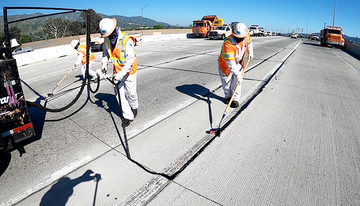 Photo of three Caltrans maintenance workers sealing cracks on Highway 99.