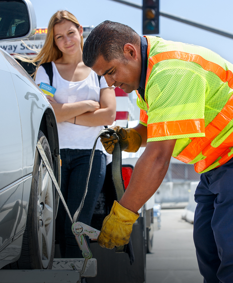 A Freeway Service Patrol worker assists woman on the highway.