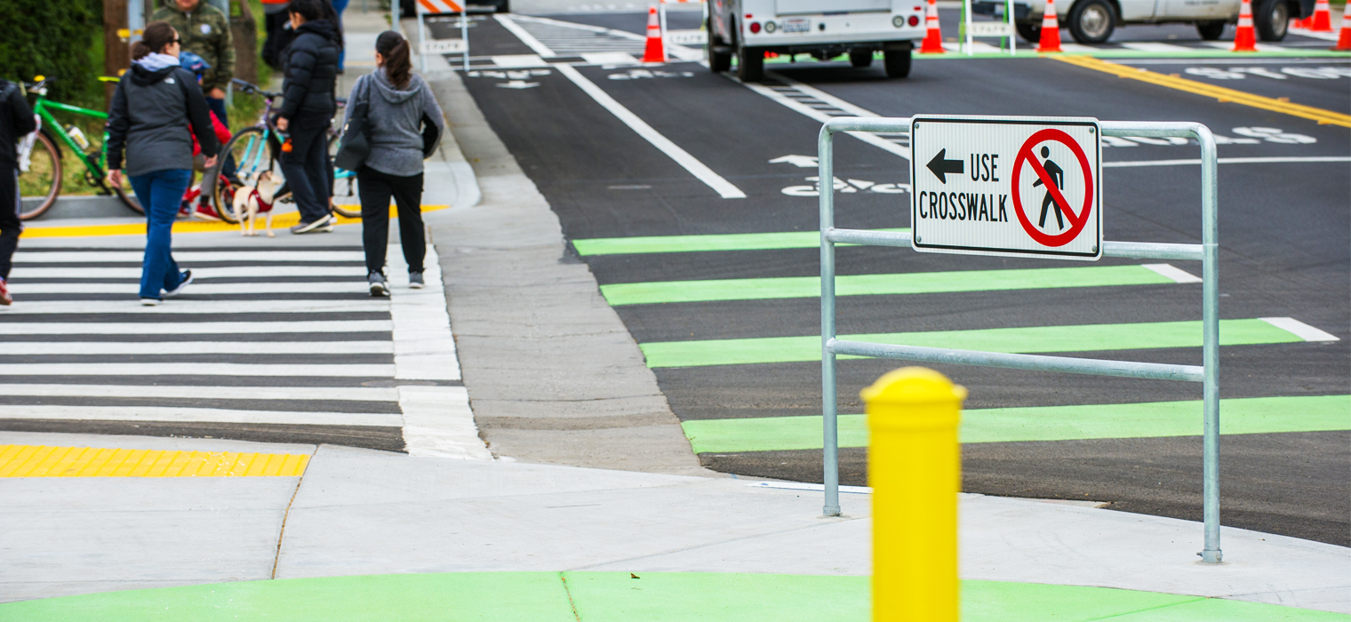 Photo of pedestrians on new crosswalk on Clark Street in E. Palo Alto. New safety features include green striping and signs.