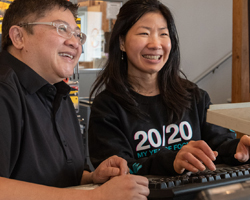 Photo thumbnail of a business owner and employee in front of a computer screen, smiling