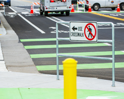 Photo thumbnail of a new pedestrian crosswalk featuring rails, signs, and road striping.