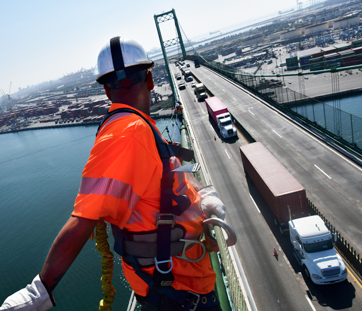 Traffic and Port of Long Beach are viewed from high up, as Caltrans workers inspect the Vincent Thomas Bridge for needed SB 1 repairs.