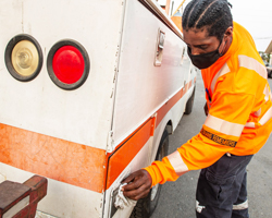 Photo of Caltrans maintenance worker, Shaun Mason cleaning the handles on a Caltrans vehicle with a disinfectant wipe.