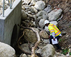 Photo of a Caltrans inspector looking over a newly installed culvert.
