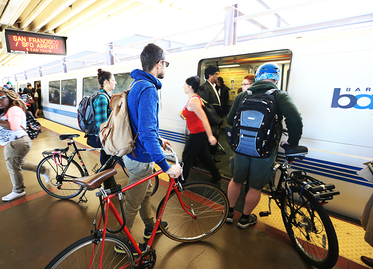 Photo taken inside a BART station in the bay area, showing passengers getting on and off the train, three people with bicycles in tow.