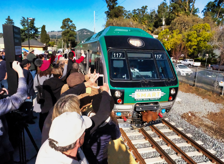 Photo of the SMART train pulling into the Novato station on opening day. A crowd of cheering people is in the foreground.