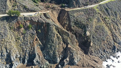 Aerial photo from February 1, 2021, showing debris up canyon and washout of California's Highway 1, on the Big Sur Coast at Rat Creek. Debris flow from the Dolan Fire burn scar washed out a 150-foot section of roadway January 28, 2021, causing a full closure.