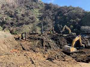 Photo from February 11, 2021, with excavators removing debris from canyon on California's Highway 1, on the Big Sur Coast at Rat Creek. Debris flow from the Dolan Fire burn scar washed out a 150-foot section of roadway January 28, 2021, causing a full closure.