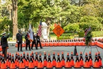 Caltrans Honor Guard members present the U.S. and California flags inside a diamond of 189 orange cones that each honor a fallen Caltrans Worker; an orange sign in the background reminds motorists to Slow for the Cone Zone - 31st Annual Caltrans Workers Memorial Ceremony April 29, 2021 - California State Capitol, Sacramento